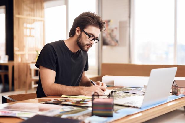 freelancer-bearded-man-taking-notes-laptop_85574-3146.jpg